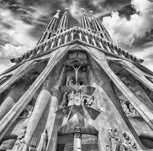 BARCELONA - AUGUST 9: The Passion Facade of the Sagrada Familia, the most iconic landmark designed by Antoni Gaudi in Barcelona, Catalonia, Spain, as seen on August 9, 2017. Cranes digitally removed Low Angle View Architecture Cloud - Sky Built Structure Belief Sky Religion Place Of Worship Spirituality Building Exterior Sculpture The Past History Travel Destinations Day Building Nature Human Representation No People Outdoors Ornate
