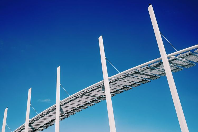 Low angle view of modern built structure against clear blue sky