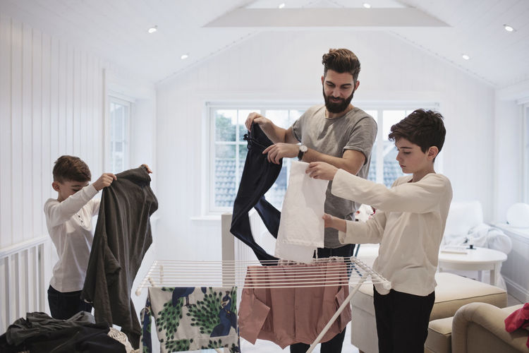 Bearded father with sons drying laundry at home