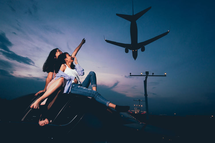 Low angle view of women pointing at airplane landing while sitting on car against sky