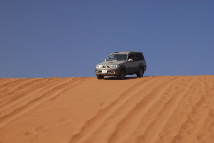 View of car on desert against clear sky