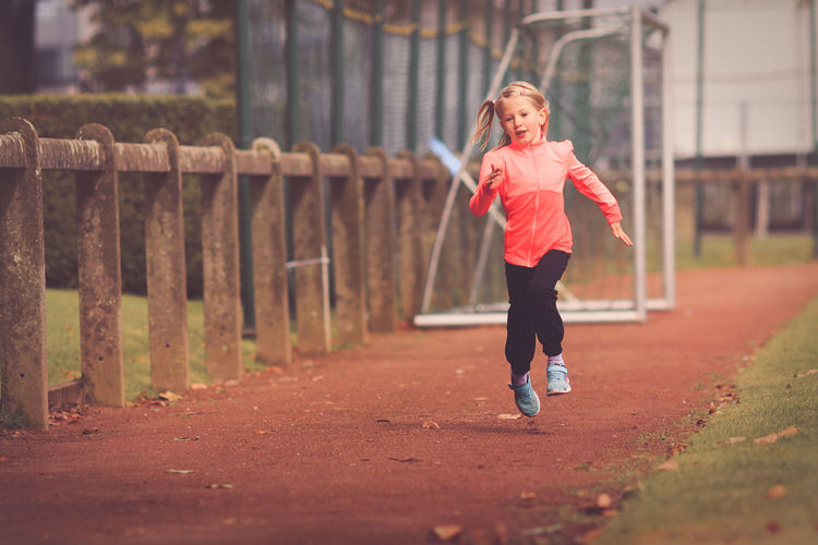 Exercising Running Age 6-9 Assertiveness Challenge Day Discipline Full Length Lifestyles One Person Outdoors People Perseverance Real People Running Running Track Sports Clothing Sports Race Track Young Girl