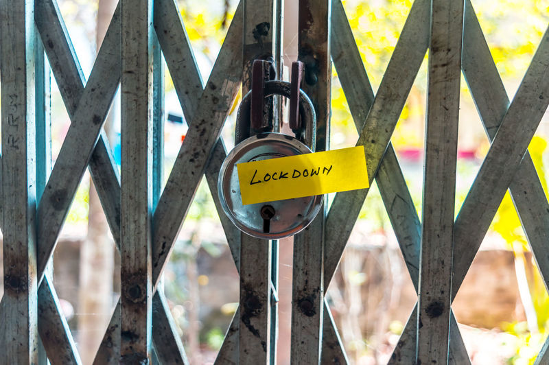 Close-up of yellow sign on fence