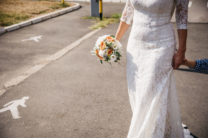 Midsection of bride holding flower bouquet while walking on road