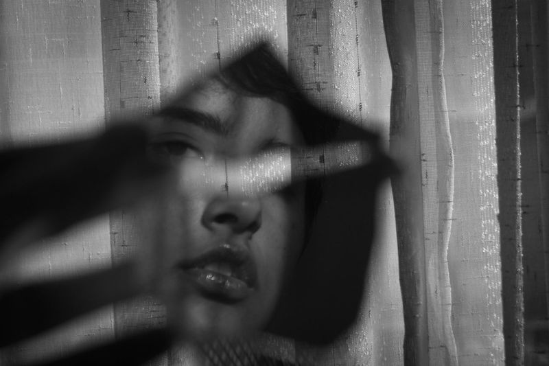 Close-up portrait of woman reflecting in mirror