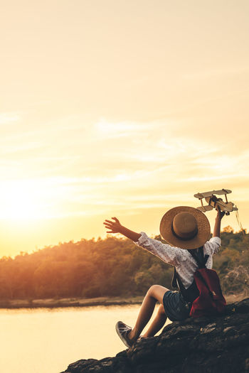 Rear view of girl with backpack holding model airplane while sitting on rock by lake against sky during sunset