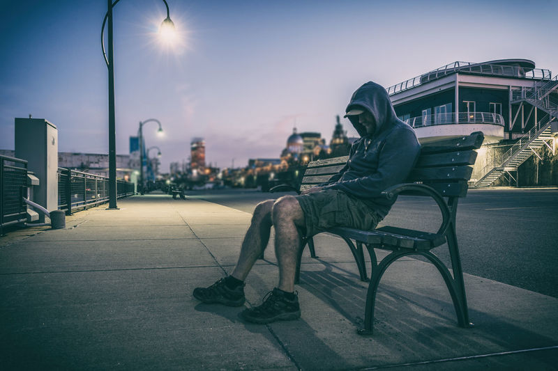 Side View Of Man Sitting In City Against Sky