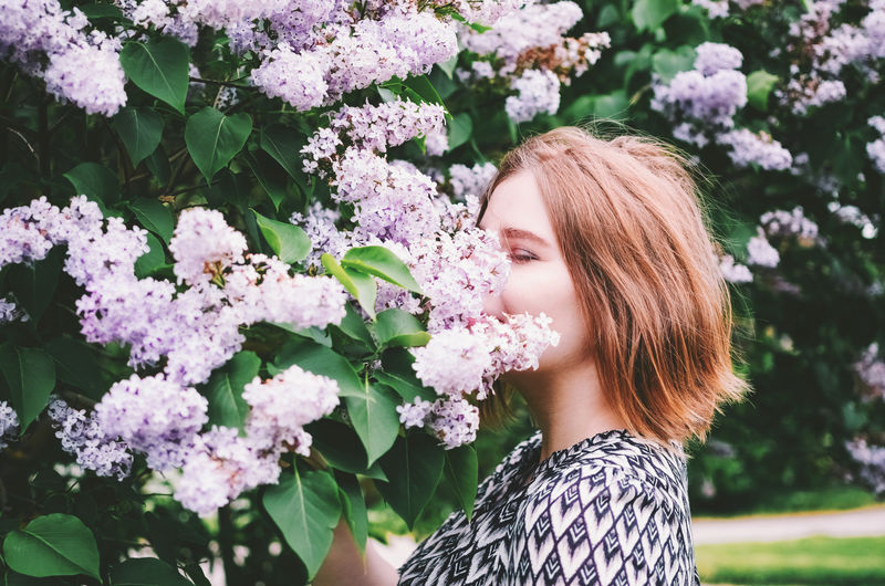 Side View Of Young Woman By Flowers
