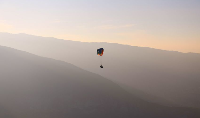 Person paragliding over mountains against sky during sunset