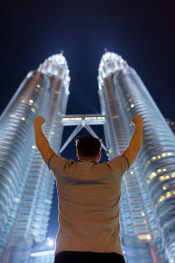Rear view of man standing against modern buildings at night