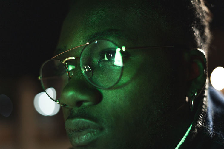 Close-up of man wearing eyeglasses in illuminated city at night