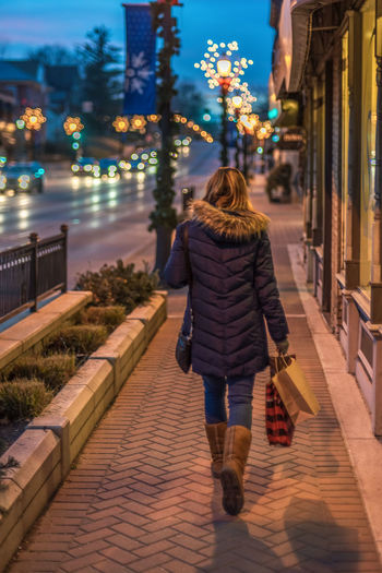 Rear view of woman with shopping bags walking on footpath