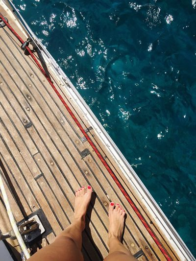 EyeEm Selects Nautical Vessel Barefoot Water Human Leg Low Section Sea Human Body Part Personal Perspective Human Foot High Angle View Transportation One Person Wood - Material Leisure Activity Mode Of Transport Boat Deck Day Real People Lifestyles Outdoors Summer Sailing
