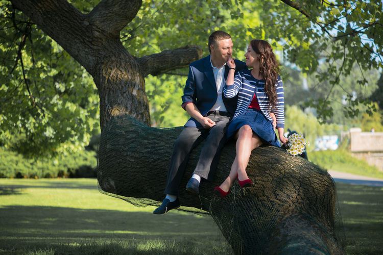 Man and woman sitting on tree trunk at park