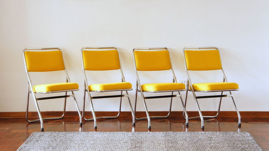 Empty chairs arranged against wall