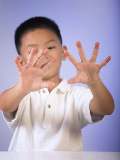Portrait of boy gesturing against wall
