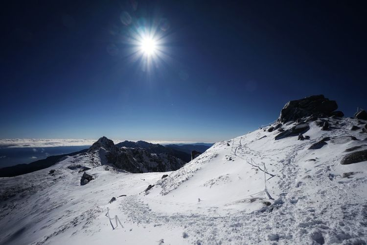 Scenic view of snowcapped mountains against clear sky during winter