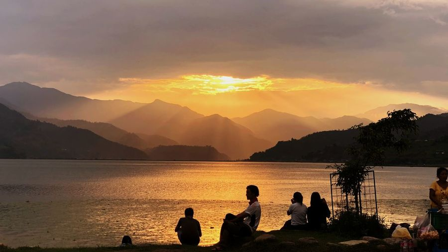 That is as awesome as an evening can a time of day! What a place to be at! Mountain Water Beauty In Nature Sky Silhouette Group Of People