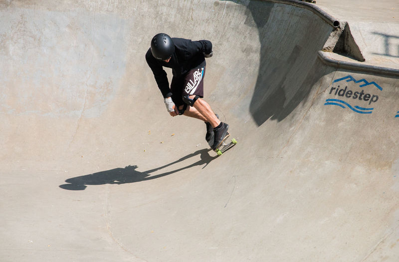man skateboarding in a skatepark One Person Skateboard Park Full Length Sport Shadow Leisure Activity Men Real People Lifestyles Skill  Day Extreme Sports High Angle View Sunlight Stunt Casual Clothing Nature Sports Ramp Skateboard Outdoors