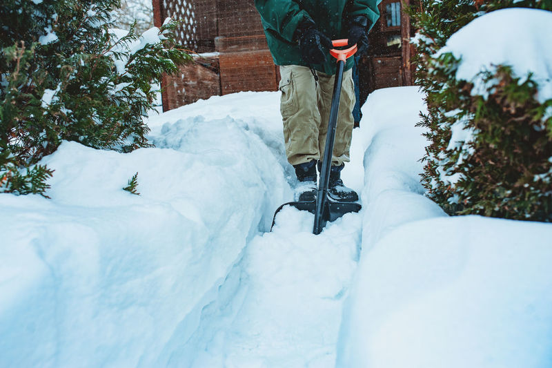 Low section of man removing snow with shovel outside house
