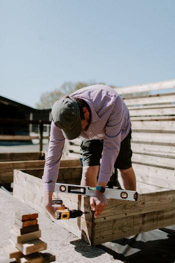 Man working on wood against sky