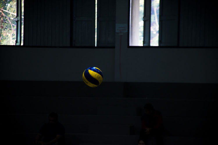 Volleyball in mid-air against windows