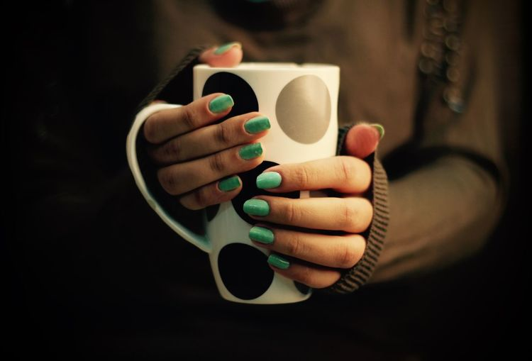 Cropped image of woman holding spotted mug