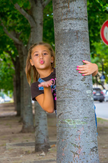 Portrait of cute girl puckering while holding tree trunk in park