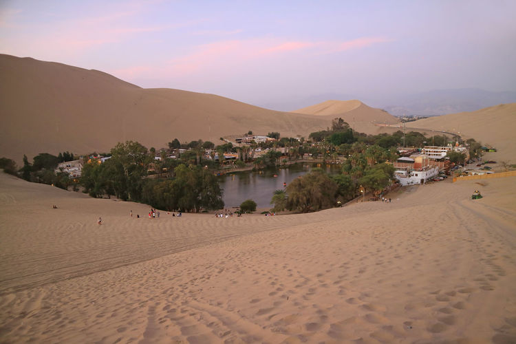 Breathtaking view of Huacachina, the oasis town as seen from the sand dune at sunset, Ica region, Peru Land Sand Scenics - Nature Nature Sky Built Structure Architecture Beauty In Nature Desert Tranquil Scene Sand Dune Landscape Water Non-urban Scene Tranquility Arid Climate Outdoors Oasis Lake Lagoon Huacachina Sunset Twilight Dusk Evening