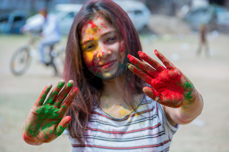 Casual Clothing Close-up Day Dirty Focus On Foreground Front View Fun Happiness Headshot Holi Human Body Part Human Hand Leisure Activity Lifestyles Looking At Camera Messy One Person Outdoors Portrait Powder Paint Real People Red Showing Traditional Festival Young Women