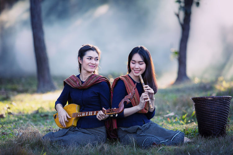 Female friends playing music while sitting on land