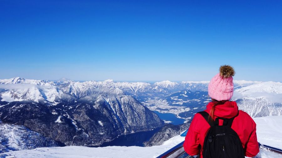 Rear view of person on snowcapped mountains against clear blue sky