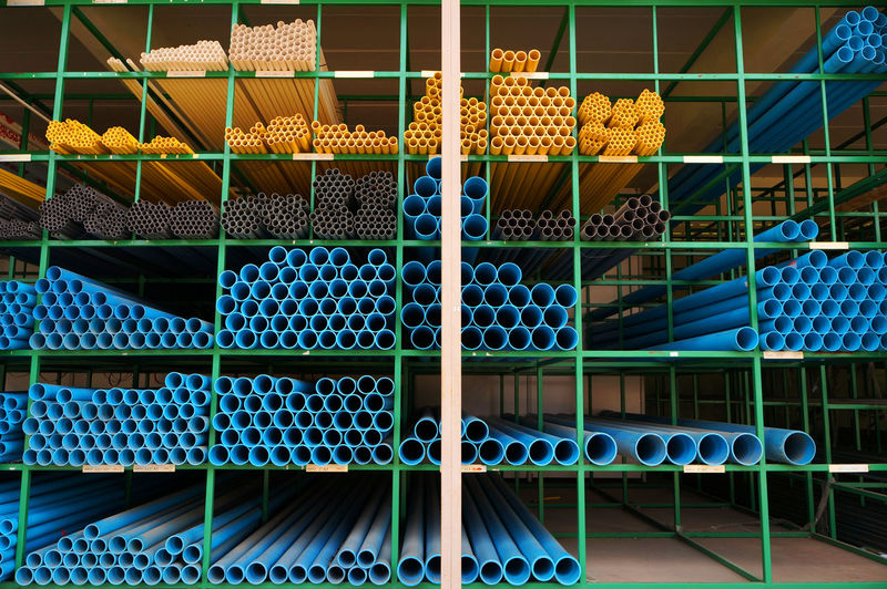 PVC pipes stacked on shelf Construction Diameter Drain Pipeline STAND Stack Storeroom Tube Arrangement Blue Choice Depot Drainpipe Godown Pattern Pipe Pvc Pipe Shelf Site Size Stack Store Storehouse Warehouse Yellow