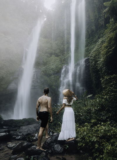 Rear view of people looking at waterfall