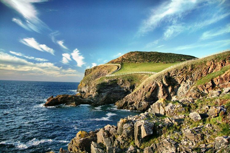 Scenic view of rocky, fenced, green coastline and sea in cornwall, uk