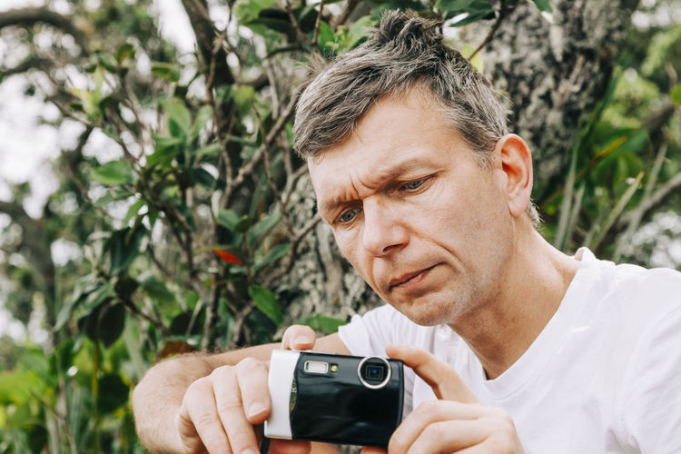Close-up of man photographing against tree