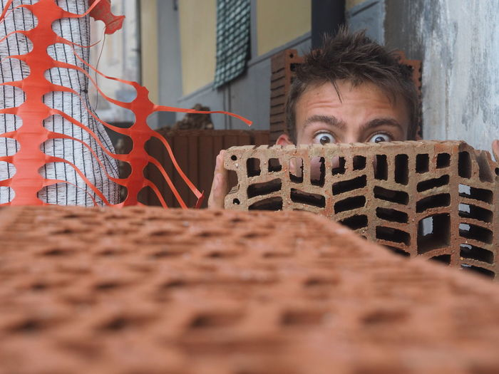Portrait of shocked young man hiding behind brick
