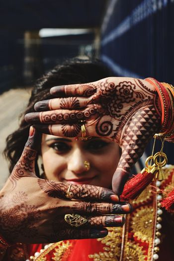 Close-up of young woman with henna tattoo gesturing outdoors