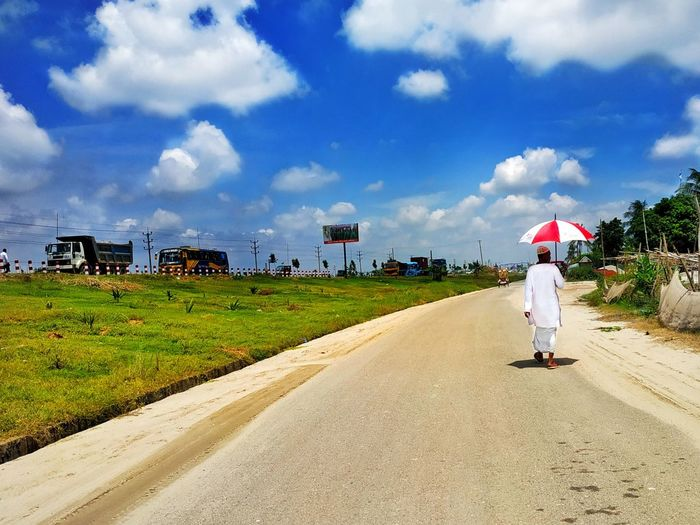Rear View Of Man Holding Umbrella While Walking On Road Against Cloudy Sky