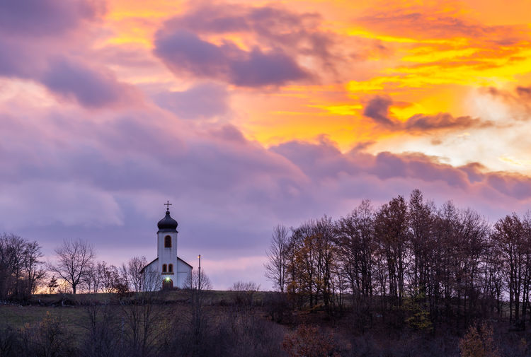 Lighthouse amidst trees and buildings against sky during sunset