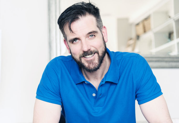 Handsome caucasian male with beard and blue eyes smiling wearing a blue polo shirt. Athletic Adult Beard Casual Clothing Caucasian Close-up Confidence  Day Handsome Happiness Indoors  Looking At Camera Mature Men Men Mid Adult Men Muscular One Man Only One Person Only Men People Polo Shirt  Portrait Real People Smiling