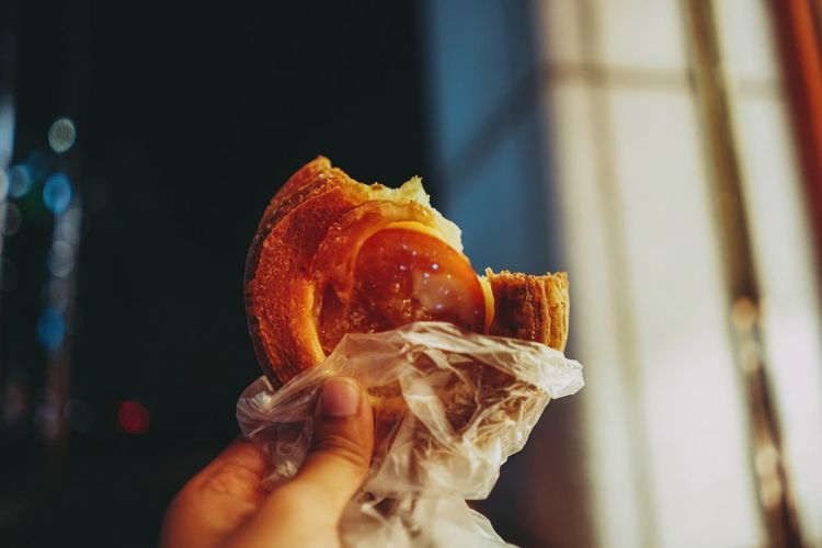 Close-up of hand holding eaten puff pastry