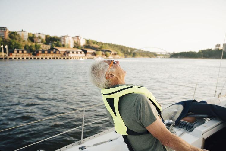 Man sailing in sea against sky