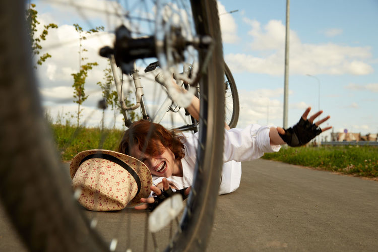 Young woman falling from bicycle on road