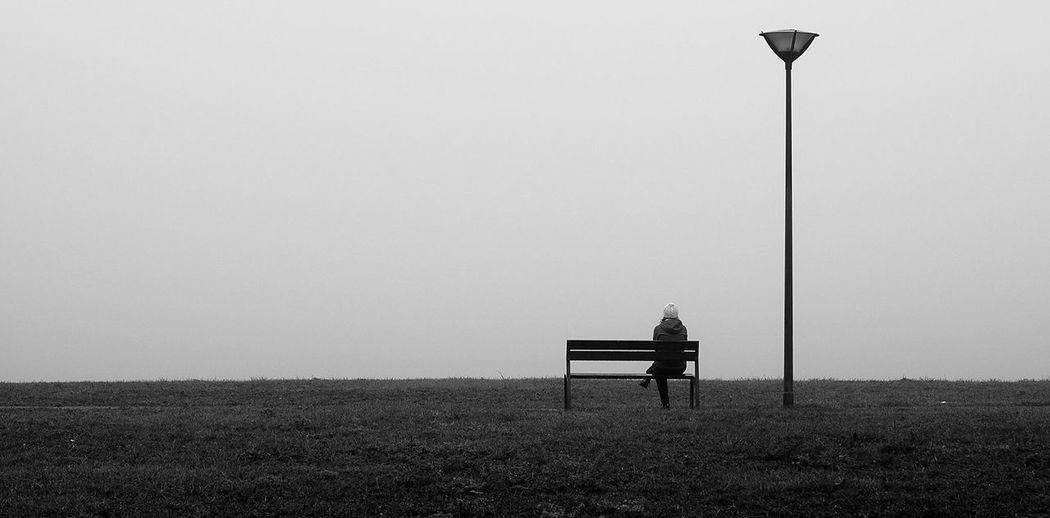 Woman sitting on bench against clear sky