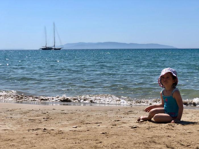 Girl sitting on shore at beach against sky