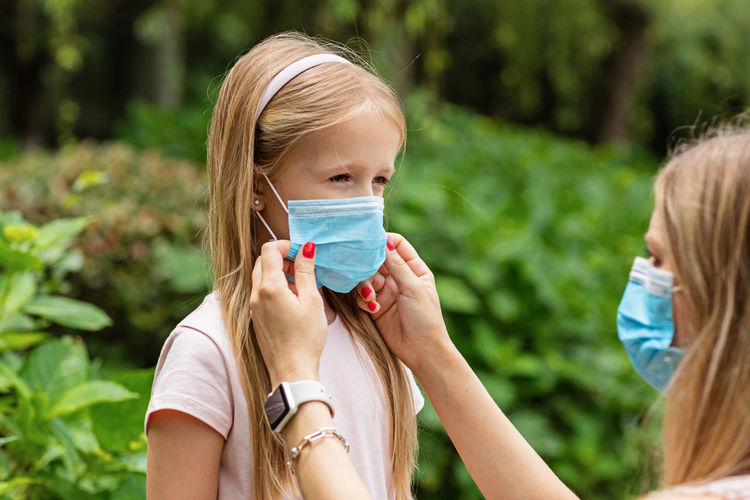 Mother putting mask on daughters face at park