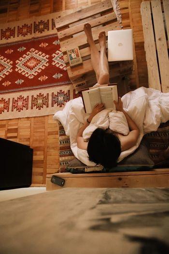 Full length of man lying on book