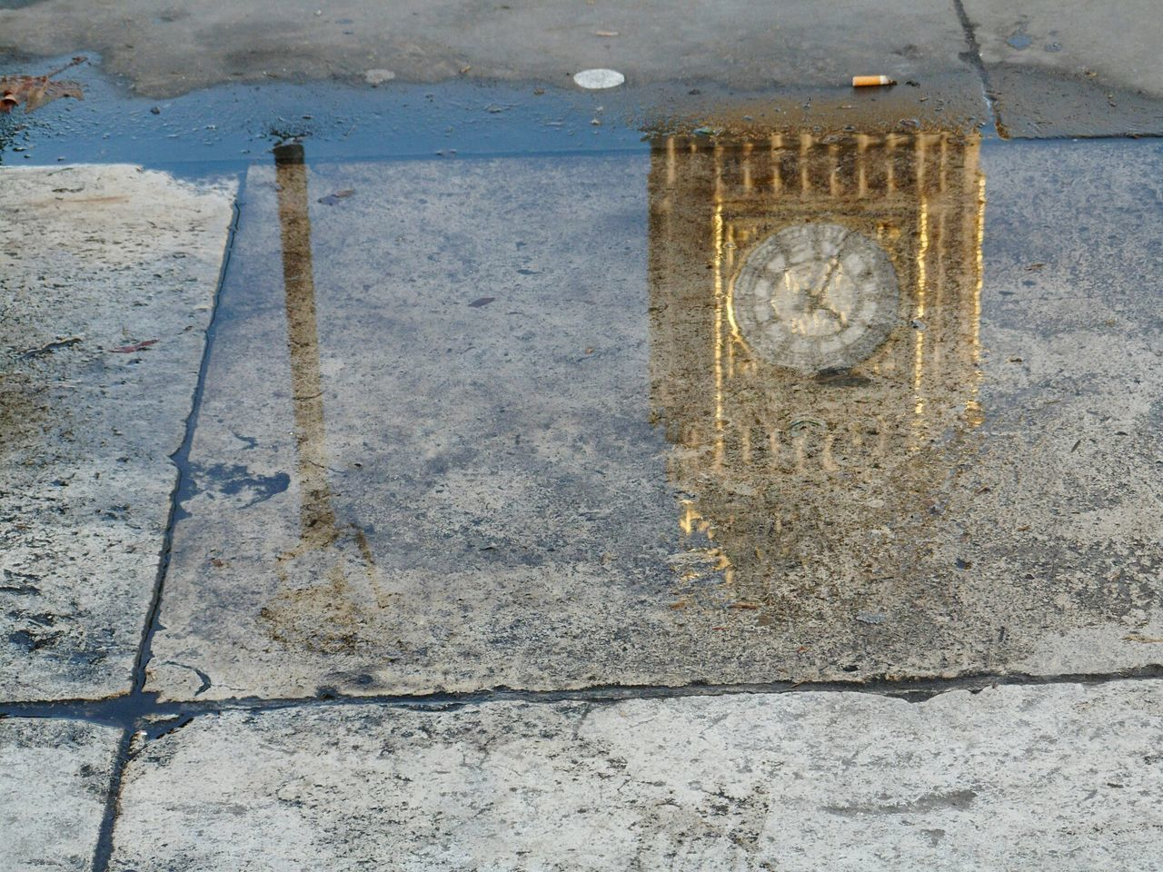 High angle view of big ben reflecting on puddle in city