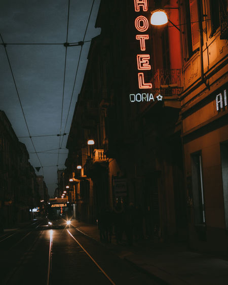 Illuminated road amidst buildings in city at night